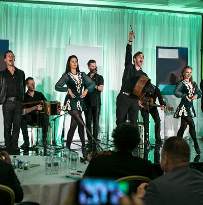 Irish dancers and musicians on a stage performing at an Orangeworks event, called Irish Tradfrest.