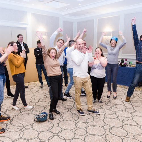 A team of delegates jumping in the air and celebrating as they completed their team development training program.