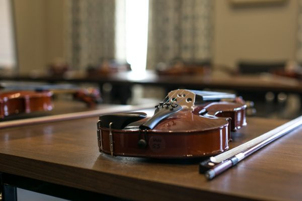 Violins laid out on the table ready for Irish TradFest where participants will learn how to play the violin.