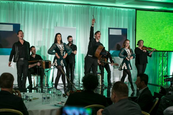 Irish dancers and musicians on a stage performing at an Orangeworks event, called Irish Tradfest.