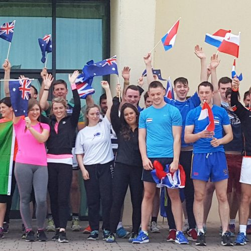 Glanbia's group of graduates smiling with a number of different flags