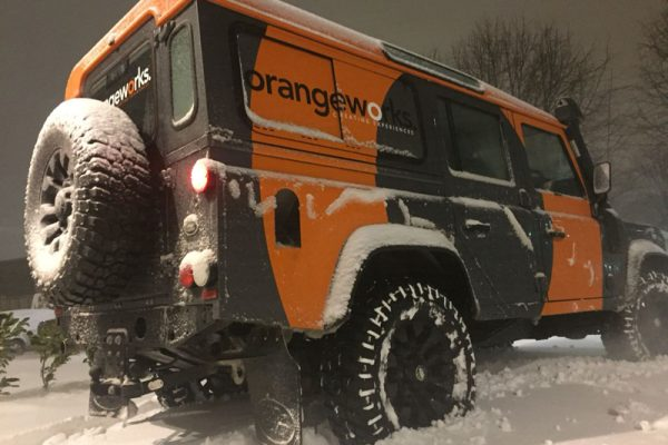 An Orangeworks landrover parked up on a snowy road showing delegates how to drive in adverse weather conditions.