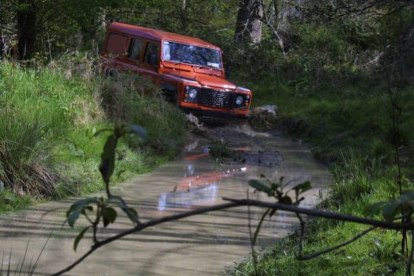 Orange Land Rover Defender driving through a muddy road during Orangeworks 4x4 off road driver Training