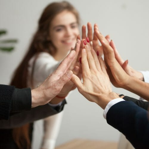 Happy colleagues high five- is employee apathy killing team performance? 5 ways to boost employee engagement