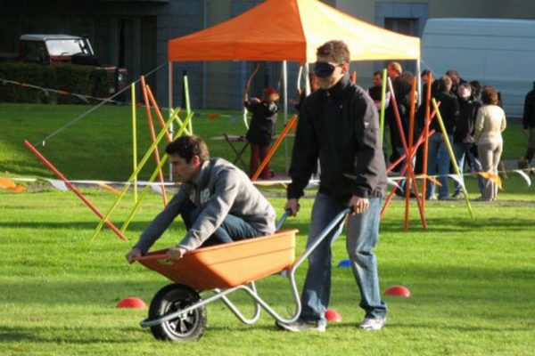 A man sitting in a wheelbarrow guiding his blindfolded driver around the Orangeworks corporate sports day obstacle course.