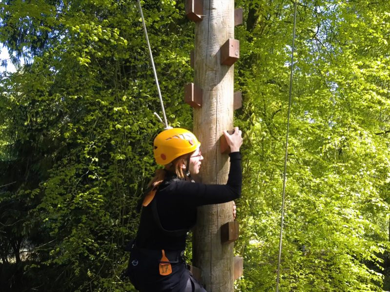A delegate climbing up the Jacobs Ladder wearing a yellow helmet, at the Orangeworks adventure course at Carton House.