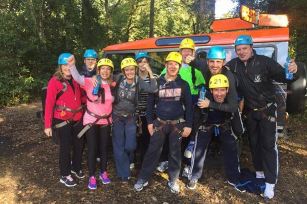 Group smiling for a photo before they take part in Orangeworks high ropes course at Carton House.