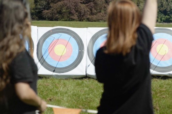 Cheerful delegates with archery targets