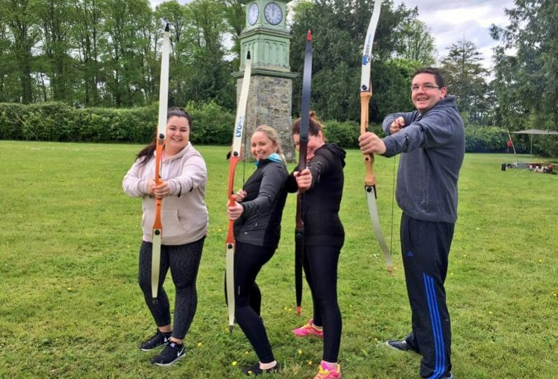 Delegates smiling while holding their archery bows as they are about to start their team building activities with Orangeworks.