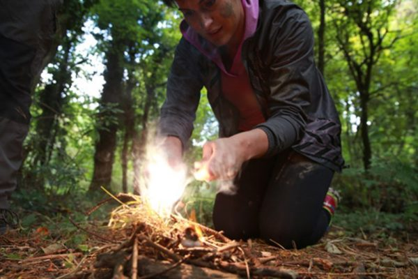 Delegate lighting her own fire which she learned how to do during the Bear Grylls survival course with Orangeworks.