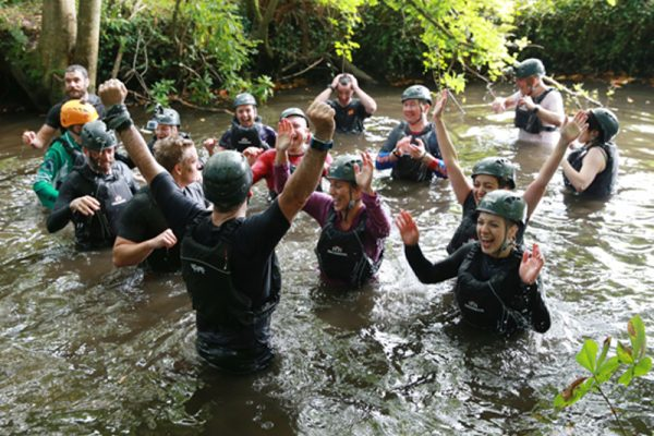 Delegates cheering in the river during our survival course: Bear Grylls Survival Academy