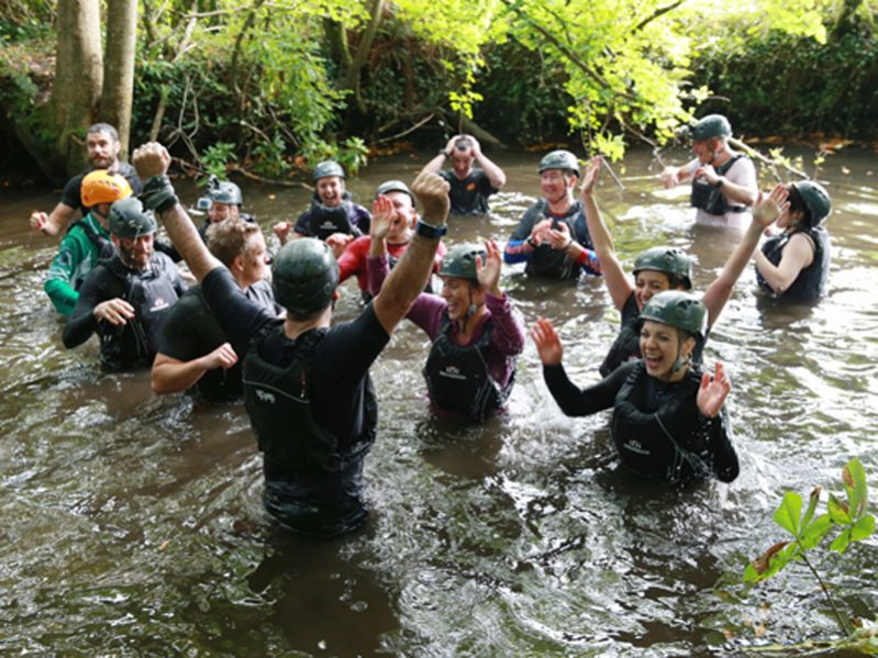 Delegates wearing wetsuits and helmets, cheering in the river during the Orangeworks Bear Grylls Survival Academy.