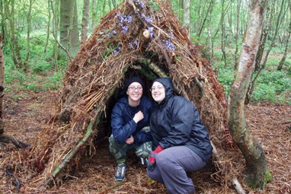 Delegates with their shelter they built during our Bear Grylls survival course