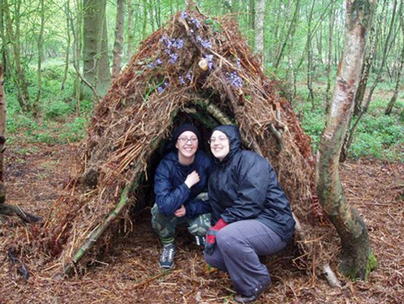 Delegates with their shelter they built out of sticks and twigs during Orangeworks Bear Grylls survival course.