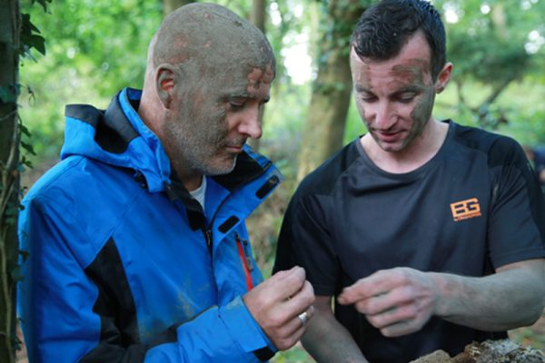 Delegate and instructor gathering insects to eat during Orangeworks survival course - Bear Grylls Survival Academy