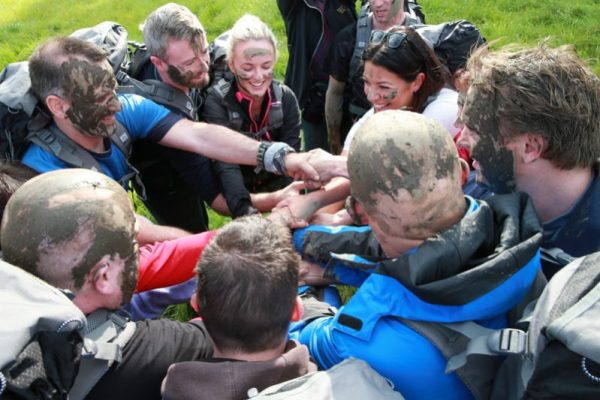 Delegates with muddy faces, join together to join hands in one circle during Orangeworks bear Grylls survival course.