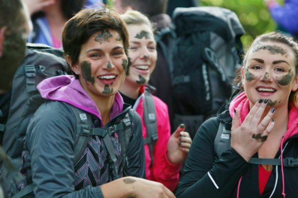 Delegates smiling with mud war paint on their face during Orangeworks Bear Grylls Survival Academy.