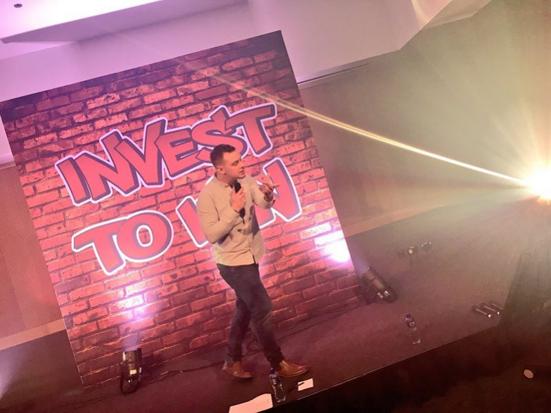 Dean, Orangeworks beatbox instructor standing on stage at a corporate conference event teaching delegates how to beatbox.