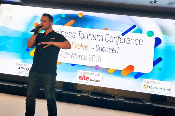 Dean, Orangeworks beatbox instructor, standing on stage at a Business Tourism Conference, teaching the participants how to beatbox.