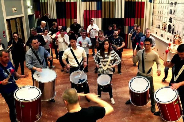 Delegates holding samba drums, watching an Orangewrosk instructor as they learn to play during Beatswork.