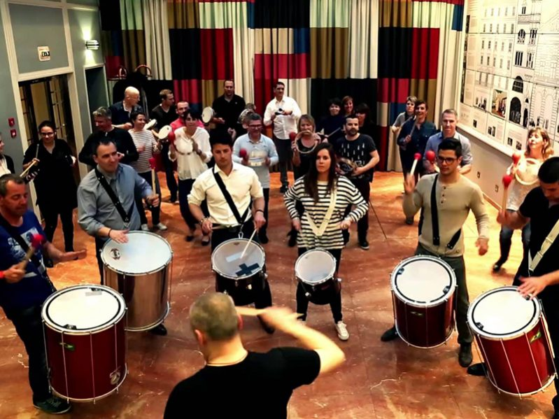 Delegates holding samba drums, watching an Orangeworks instructor as they learn to play during Beatswork.