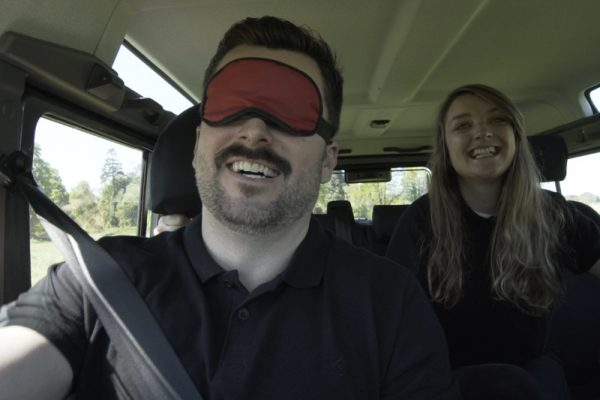 Delegate smiling while being directed around a 4x4 obstacle course, during Blindfold Driving with Orangeworks.
