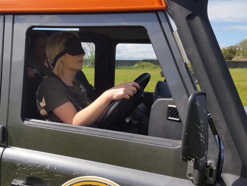 A Blindfolded driver in an Orangeworks Landrover Defender, being guided by teammates on how to drive the obstacle course.