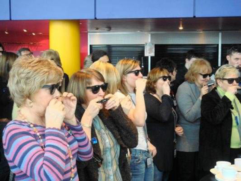 Ladies with glasses on learning how to play the harmonica during Orangeworks music-themed team engagement activity.