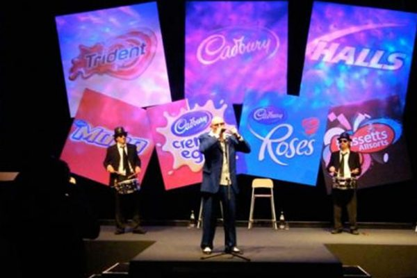 The Cadbury's team performing with harmonicas on stage with signs behind them at their team bonding event by Orangeworks.