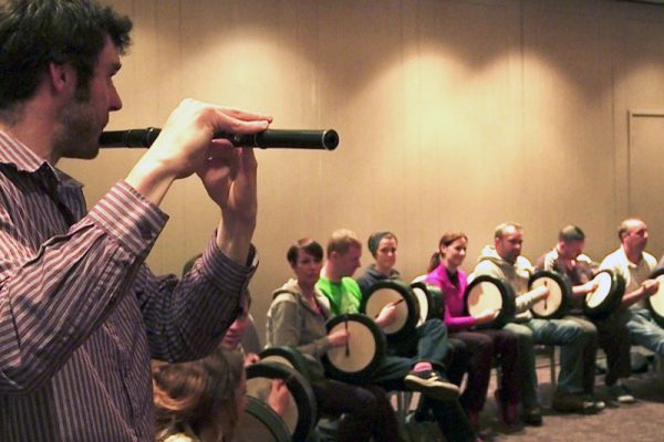 A man playing the flute while other people sitting play the bodhran as part of the Orangeworks team building activity.