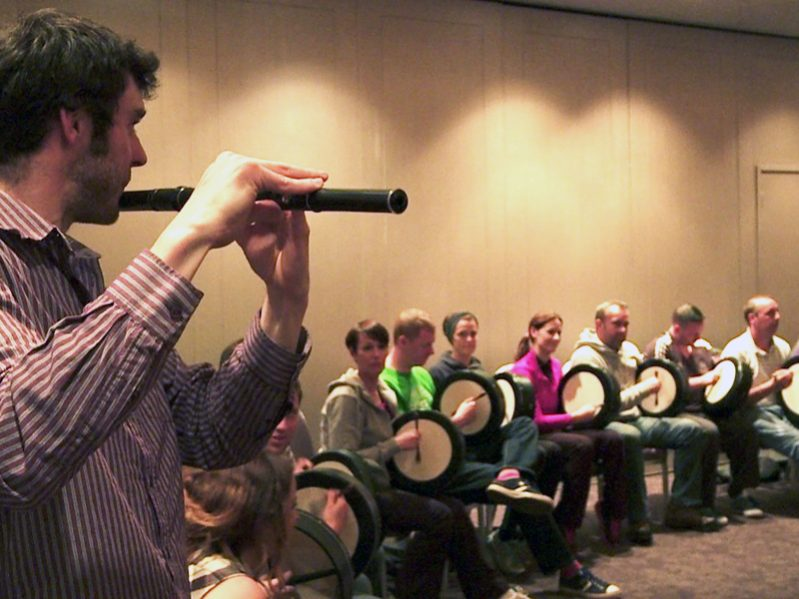 A man playing the flute while others are sitting playing the bodhran as part of the Orangeworks team building activity.