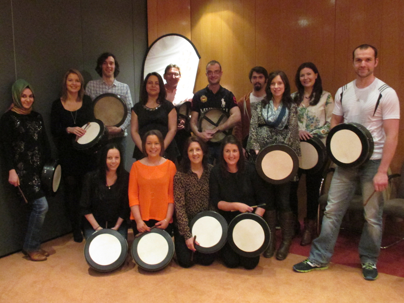Delegates holding their bodhrans and smiling after they finished the Bodhran workshop, a team-building event by Orangeworks.