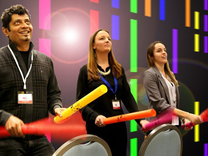 Participants holding colourful boom whackers and hitting them off the chairs during the finale of their conference energiser, BoomTime.