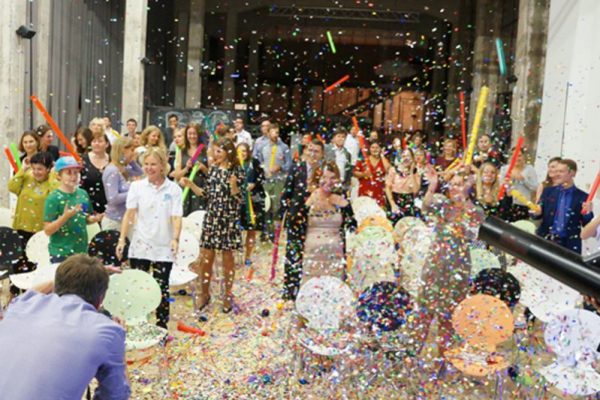 Confetti falling as the participants of Boom Time celebrate the finale of a conference energiser while playing music with their boom whackers.