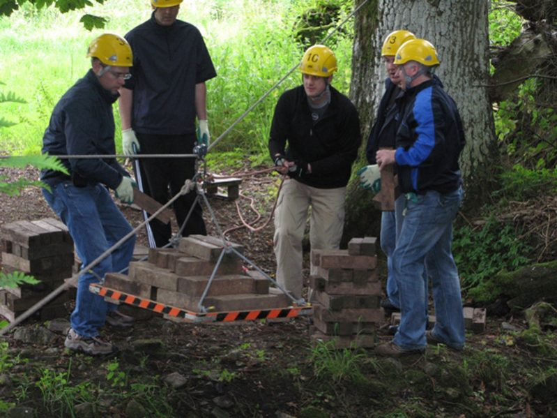 Team working together to transport logs across the river during Bridge Building, a team development challenge with Orangeworks.