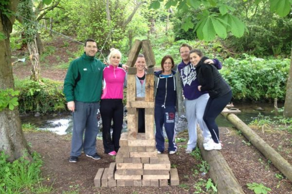 Delegates smiling with their tower of wooden logs, for bridge building, an outdoor team building adventure game.
