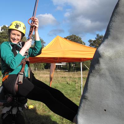 Delegate smiling whilst climbing Orangeworks Mobile Climbing Wall