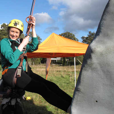 Delegate smiling whilst climbing our Mobile Climbing Wall
