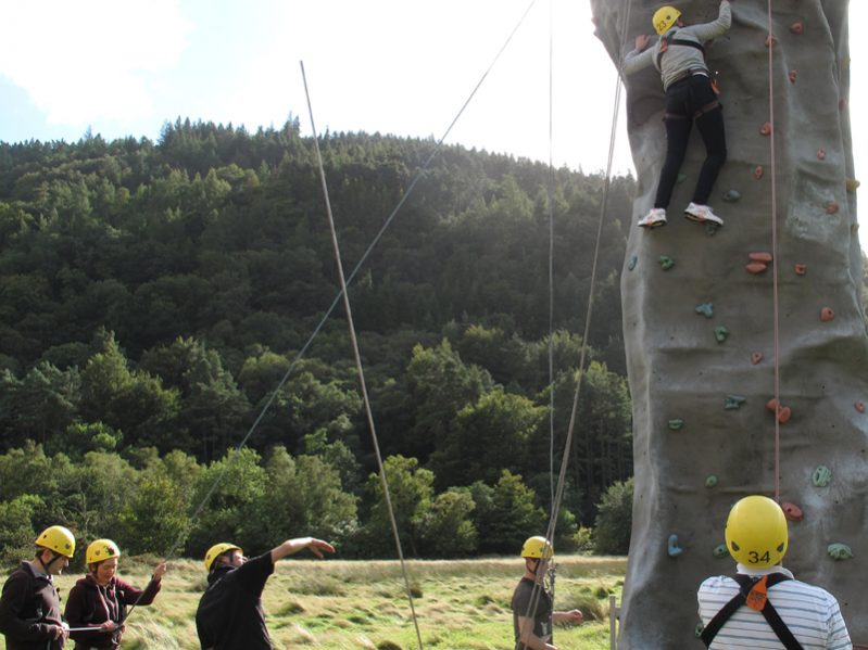 Delegates working together to help their team climb Orangeworks Mobile Climbing Wall