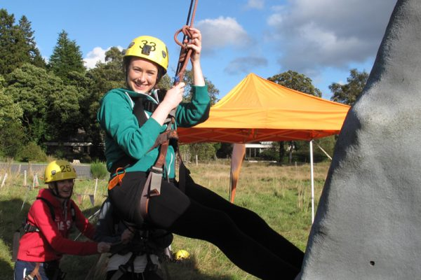 Delegate smiling climbing our Mobile Climbing Wall