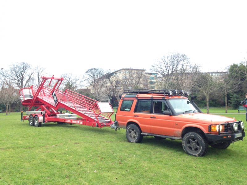 Orangeworks orange Landrover Defender transporting our Mobile Zip Line