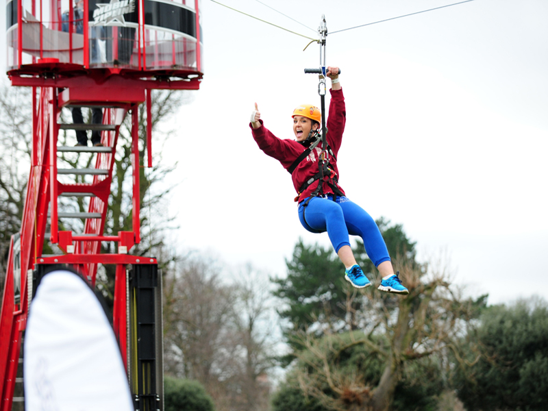 Delegate giving thumbs up whilst going down the Orangeworks Mobile Zip Line
