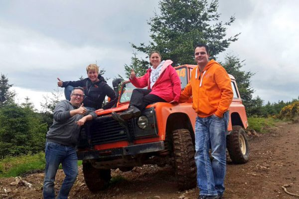 Delegates smiling with one of Orangeworks orange Landrover Defenders after their 4x4 off road driving experience.