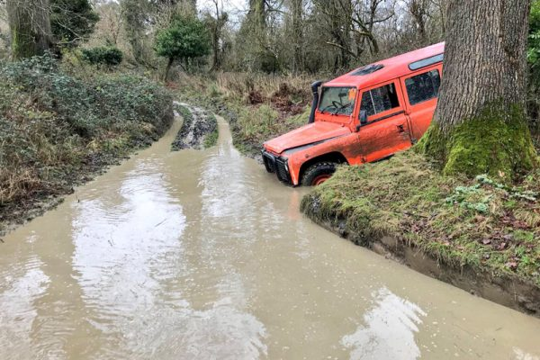 Orange Landrover Defender about to drive onto our swamped tracks