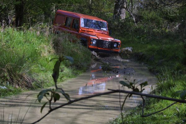 Orange Landrover Defender driving through some water