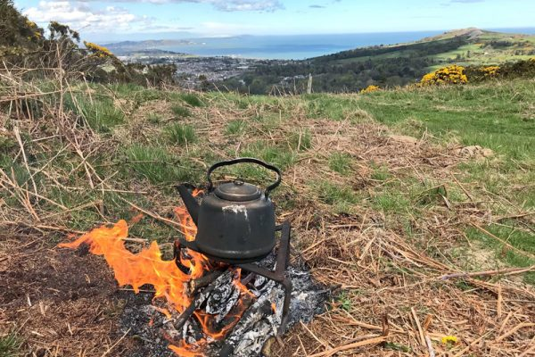Fire lighting with a tea pot heating in the wilderness. Bear Grylls Survival Course Ireland