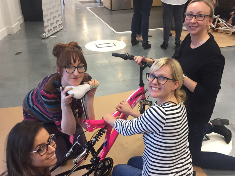 Team smiling while building their bike in Charity Bike Build, a team-building activity that gives back to the community.
