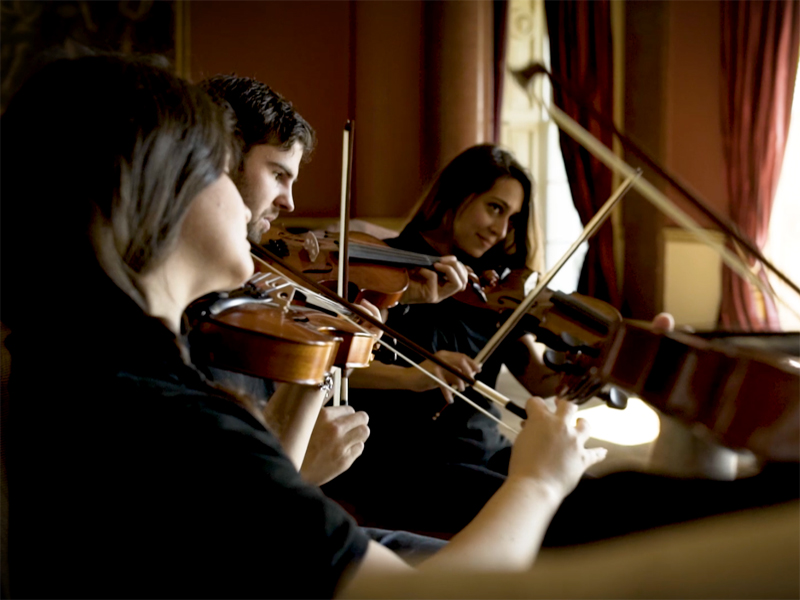 3 delegates of the team building challenge Crescendo, powered by Orangeworks, learning how to play the violin.