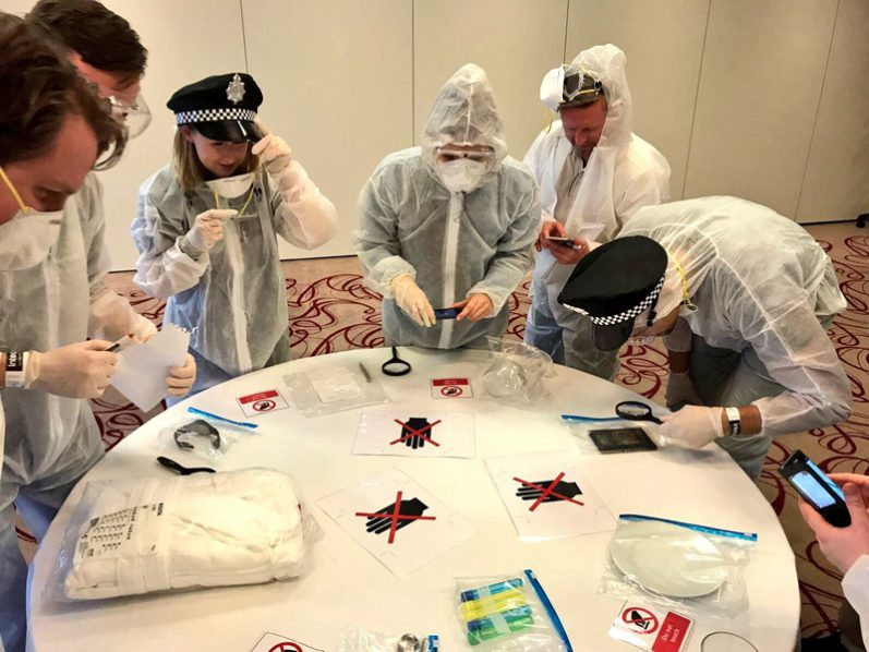 Delegates examining evidence while wearing white overalls during the forensic style team building activity by Orangeworks.