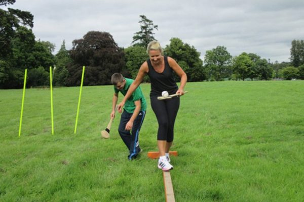 Delegate balancing on a wooden plank whilst holding a slitter on a hurl during the Irish hurling workshop with Orangeworks.